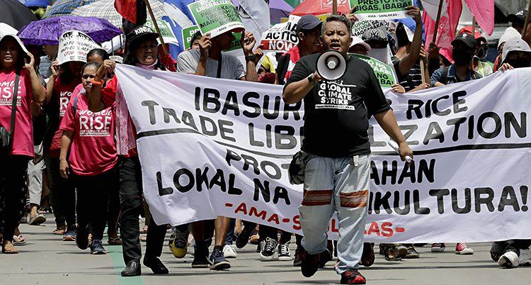 Människor går i en klimatprotest. De har skyltar med olika budskap. En man går först.