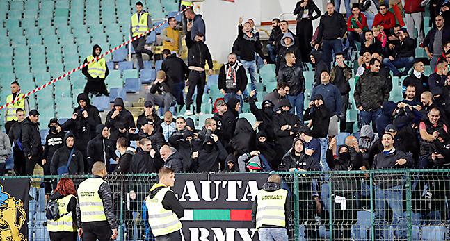En fotbollsläktare med svartklädda människor i publiken.