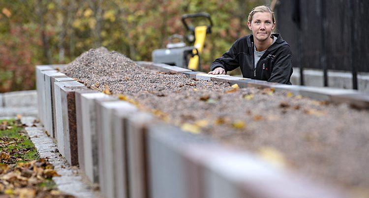 Rebecka Hansson syns bakom en rabatt av stenar.