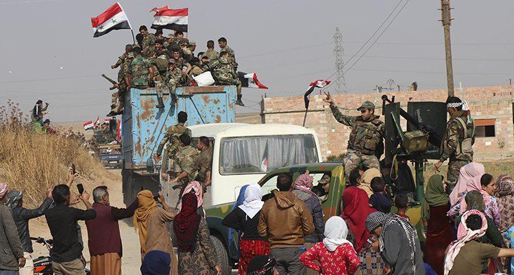 Bild från när syriska soldater kom till norra Syrien. De åker lastbil. Många människor tar bild på dem.