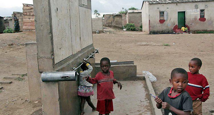 Barn i Zambia leker utomhus. Husen runt dem är slitna.