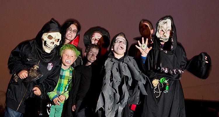 En grupp med barn som vill skrämmas. Några har på sig dödskallemasker och några har huggtänder.