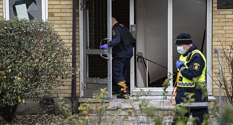Två poliser vid huset. Alla fönster i dörrarna är trasiga.