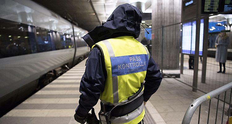 Ryggen på en man med gul väst där det står passkontroll.