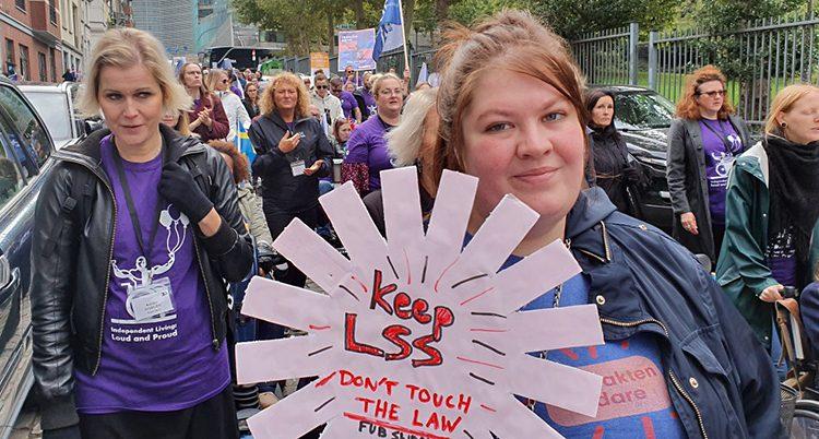 Flera personer har skyltar i händerna. De går på en gata i Bryssel och demonstrerar.