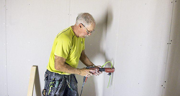 En äldre man snickrar. Han borrar i en vägg.