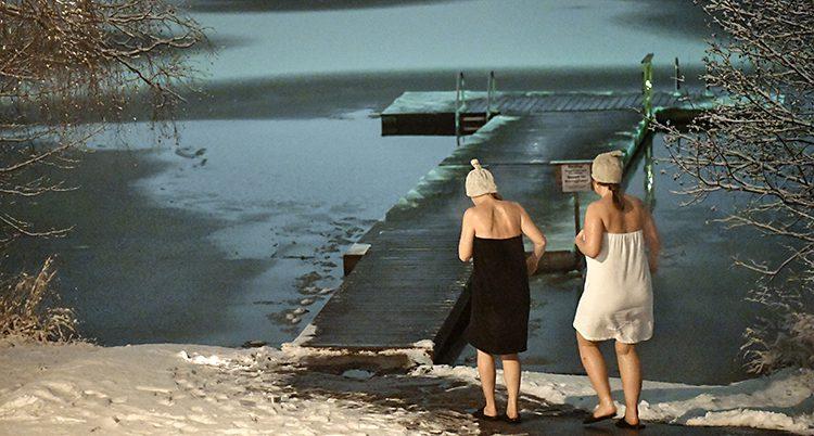 Två kvinnor har mössa på huvudet. De går ner till vattnet och en brygga för att bada. Det är snö på marken.