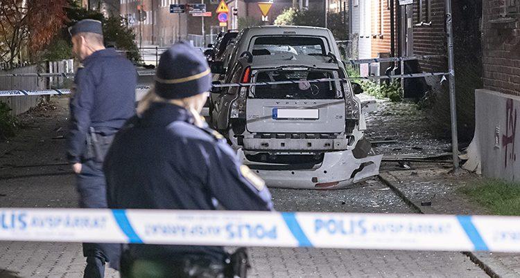 Poliser har spärrat av en gata med blåvita band. En polisrygg i förgrunden. En skadad bil i bakgrunden.