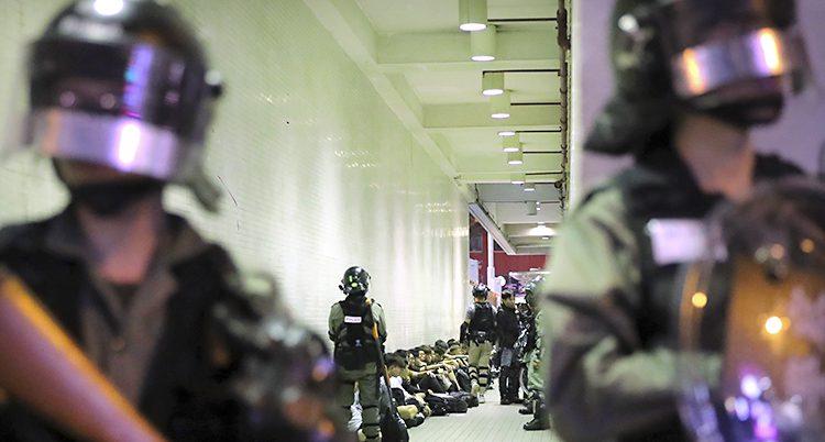 Ungdomarna sitter på golvet i en korridor. Poliser med vapen står runt dem