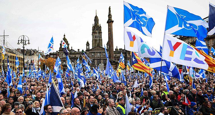 Massor av människor med flaggor står på ett torg