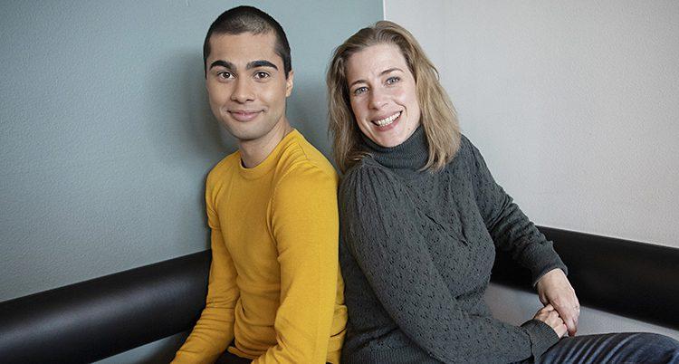 En unga kille i gul tröja sitter bredvid en lite äldre kvinna i grå polo
