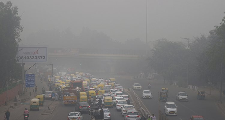 Bilar åker på en väg i staden Delhi. Luften är mycket grå.