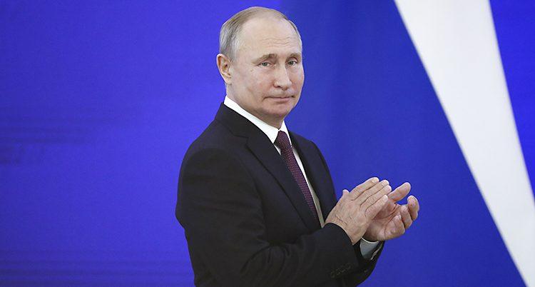 Vladimir Putin står framför en blå vägg och tittar åt sidan