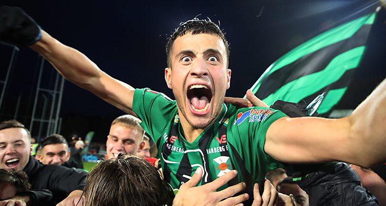 En spelare i laget Varberg jublar tillsammans med fans. Spelaren skriver av glädje och tittar in i kameran. Han har på sig en tröja som är randig i grönt och svart.