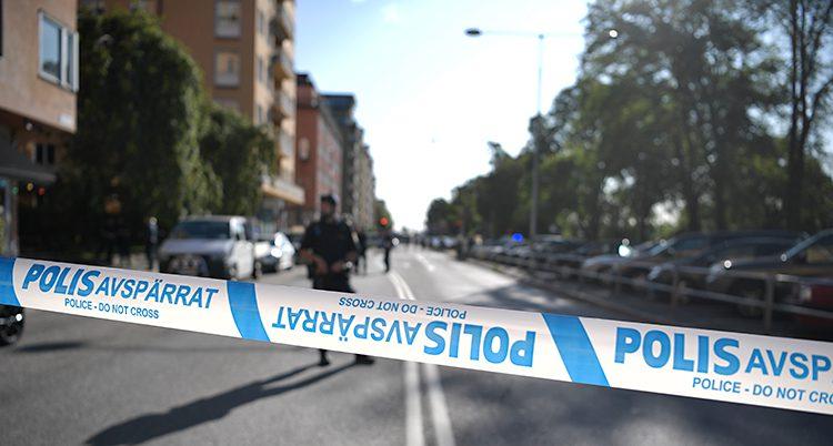 Bilden visar en gata i Stockholm. På ena sidan av gatan syns en rad med lägenhetshus. Polisen har satt upp ett avspärrningsband. I bakgrunden syns en polis som vaktar.