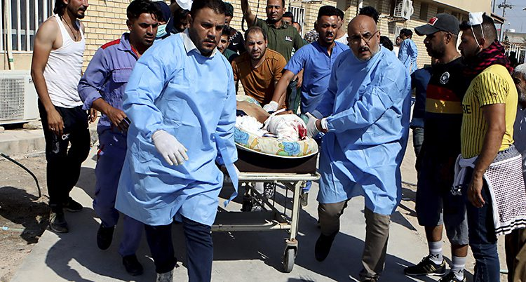 Blåklädda personer drar en sjuksäng med en skadad person.