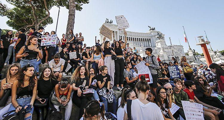 Flera ungdomar demonstrerar i staden Rom i Italien.