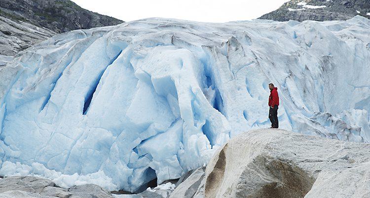 En person står vid en stor norsk glaciär.