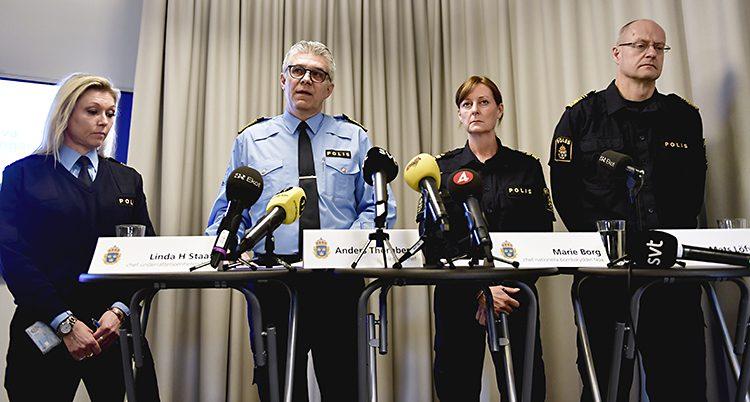 En bild från en presskonferens. Fyra chefer i polisen står vid ett bord och pratar. Det är två kvinnor och två män. På bordet finns flera mikrofoner från journalisterna.