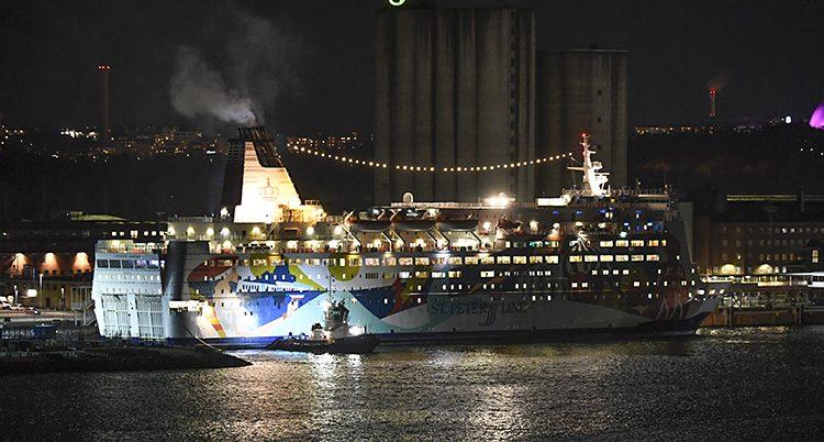 Det är kväll. Det lyser från färjans fönster. Den står stilla i en hamn.