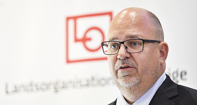 En man i 50-årsåldern som står framför en vägg där det står Landsorganisationen i Sverige. Mannen är flintskallig med kortklippt hår på sidorna. Han har glasögon och ett kort skägg runt munnen.