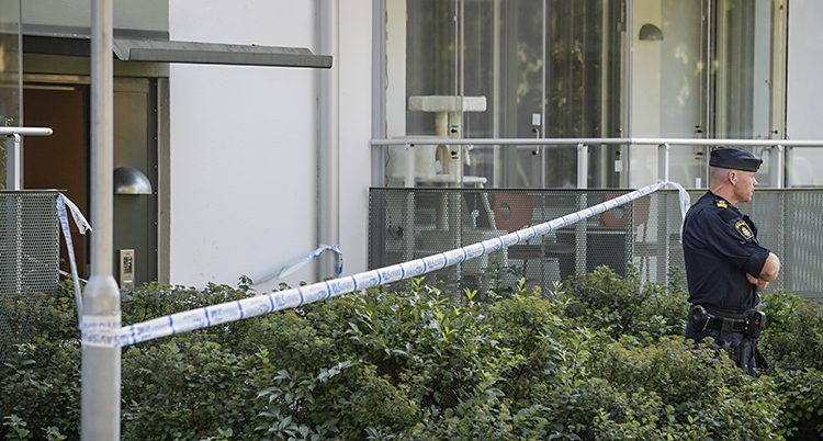 Poliser har spärrat av runt ett hus med lägenheter. Utanför huset står en polis och vaktar.