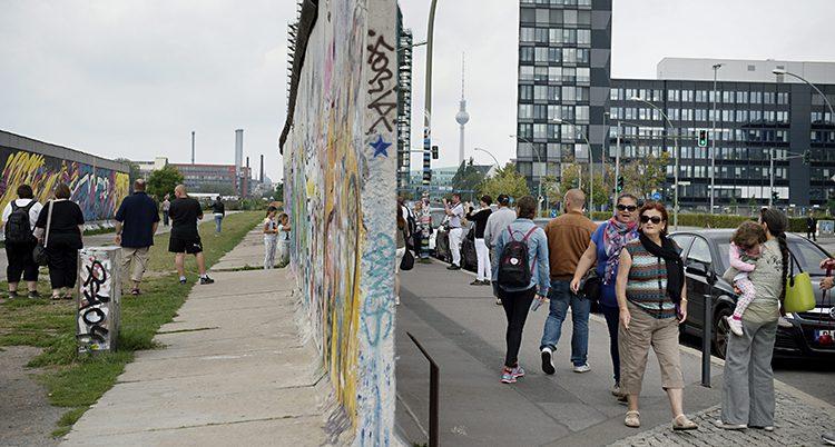 En bit av en mur är målad på. Människor går bredvid och tittar