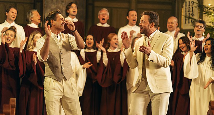 Peter Jöback sjunger tillsammans med en kör i kyrkan. Han är klädd i vitt.