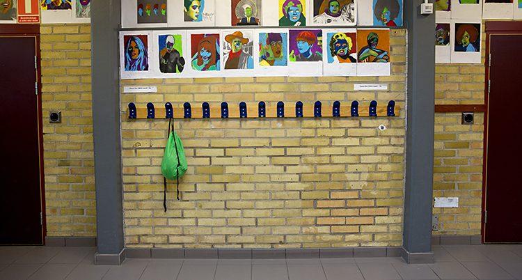 En gul tegelvägg inuti en skola. Där sitter klädhängarna. På en av dem hänger en grön ryggsäck. Ovanför hängarna sitter en massa teckningar.