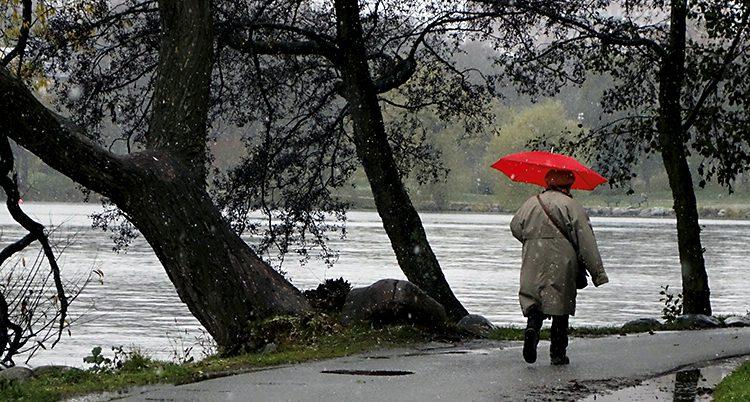 En kvinna promenerar. Hon har ett rött paraply i handen.
