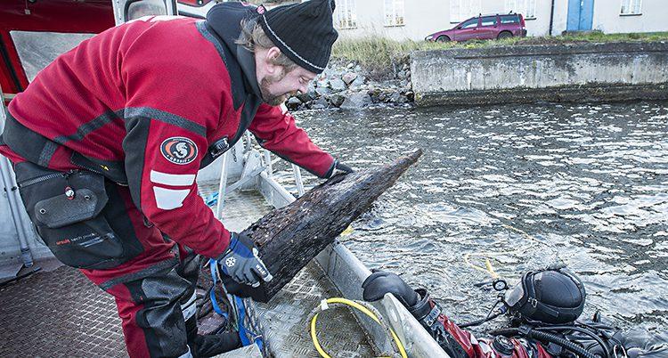 Jim Hansson tittar på en av delarna de har hittat utanför Vaxholm.
