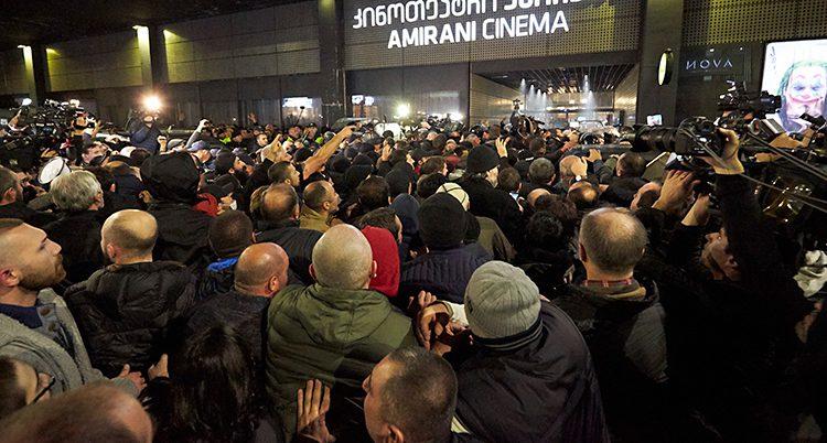Upprörda människor trängs framför biograf.