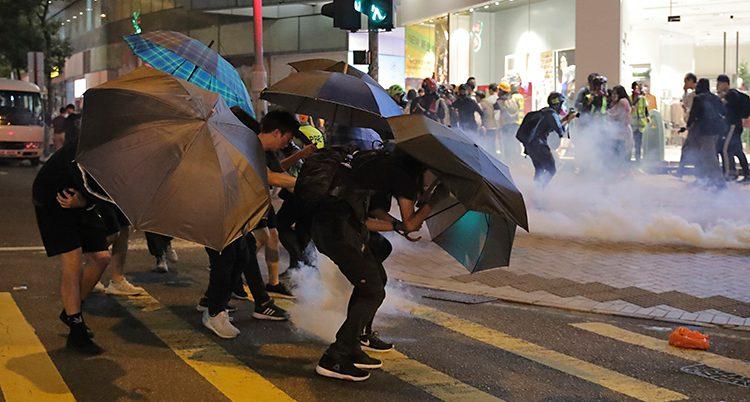 En gata i Hongkong på kvällen. Det syns tårgas på gatan. Längre bort syns poliser. Närmaste i bild står några människor med paraplyer.