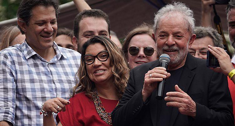 Han pratar i mikrofon och många glada människor står runt honom