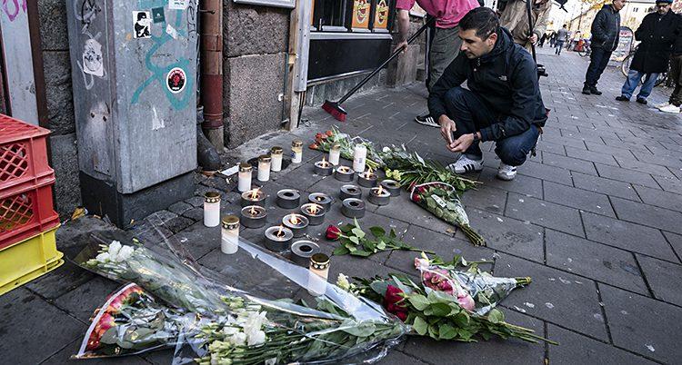 En man sitter på hus på trottoaren. Framför honom finns blommor och ljus.