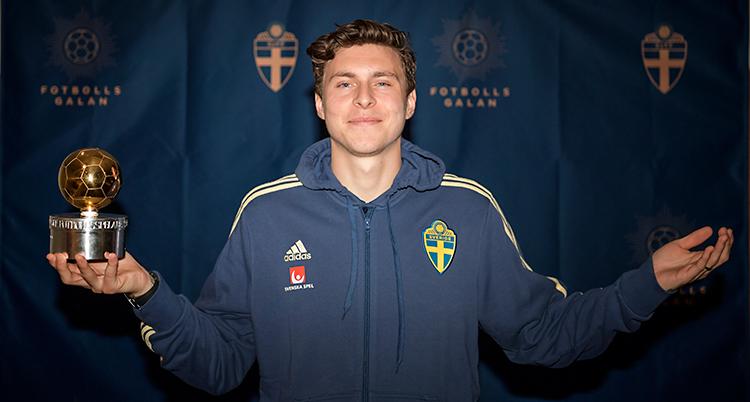 Victor Nilsson Lindelöf visar upp sitt pris Guldbollen. Han har på sig en träningsjacka.