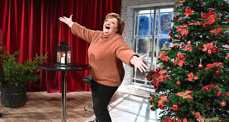 Skådespelaren Marianne Mörck ler och sträcker ut båda armarna. Hon står i ett rum med ett rött draperi och en julgran med dekorationer.