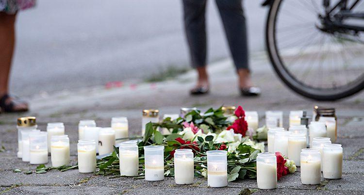 Bilden visar en trottoar. Där finns det blommor och flera tända ljus. Två personer och en cykel står lite längre bak. Man ser bara benen på personerna.