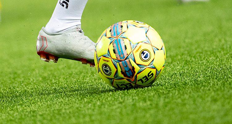 Bilden visar en fotbollsplan. Där syns en gul fotboll och nederdelen av ett ben. Personen har vit strumpa och en fotbollssko på sig.