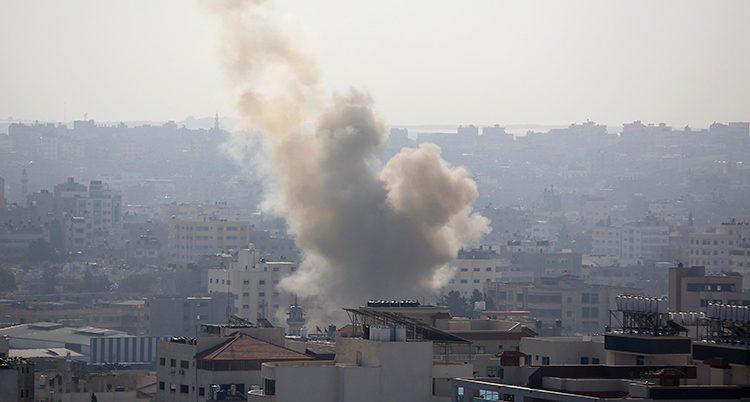 Hustak i staden Gaza City. Ett stort rökmoln stiger mot skyn från staden.