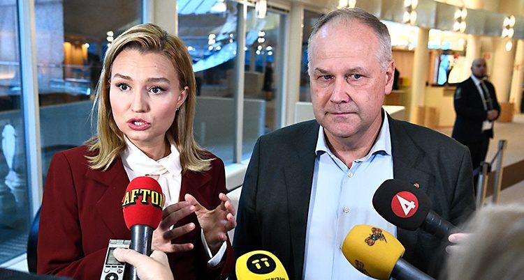 Ebba Busch Thor och Jonas Sjöstedt blir intervjuade tillsammans av flera journalister. Journalisterna sträcker fram mikrofoner mot dem. Ebba Busch Thor har långt blont hår och en röd kavaj. Jonas Sjöstedt har kort grått hår och en svart kavaj.