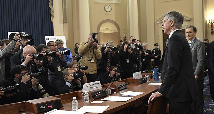 En massa fotografer tar bilder av två man bakom ett skrivbord.