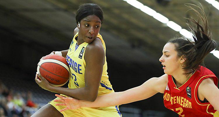 Bilden är från en basketmatch mellan Sverige och Montenegro. Sveriges spelare Binta Drammeh håller undan bollen. En spelare från Montenegro försöker ta bollen.