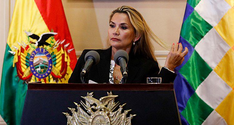 Jeanine Áñez står i en talarstol och pratar. Hon har långt blont hår och en svart kavaj. I bakgrunden syns flaggor, bland annat den bolivianska flaggan.