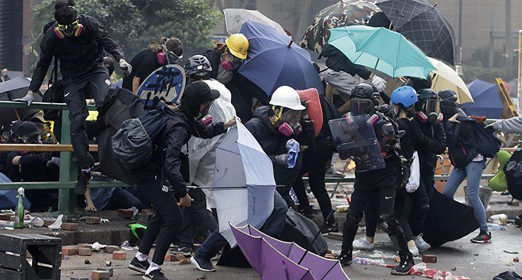 Människor med hjälmar och masker håller på att klättra över ett staket.