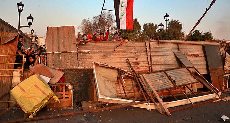 Bilden visar en väg i Bagdad. Folk som protesterar har ställt upp en blockad av trä och annat. Bakom blockaden står demonstranter. De har också en irakisk flagga.