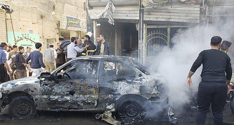 Det ryker från resterna av en bil. Bilen är helt sönderbränd. Människor står i grupper och pratar.