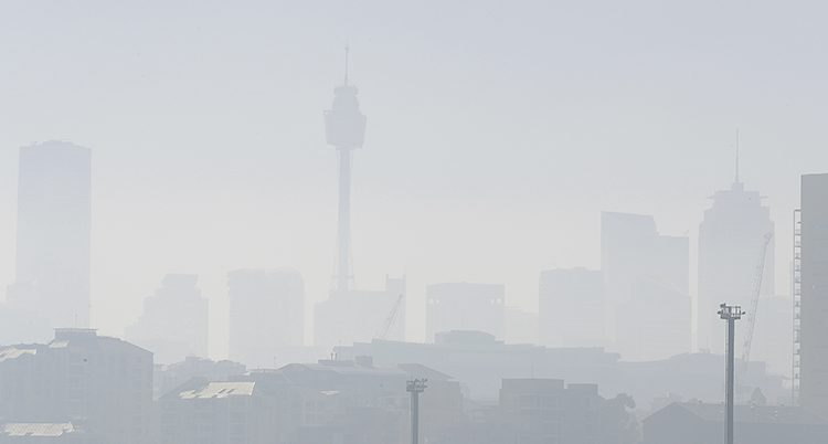 Byggnader skymtar. Luften är full av dimma och rök.