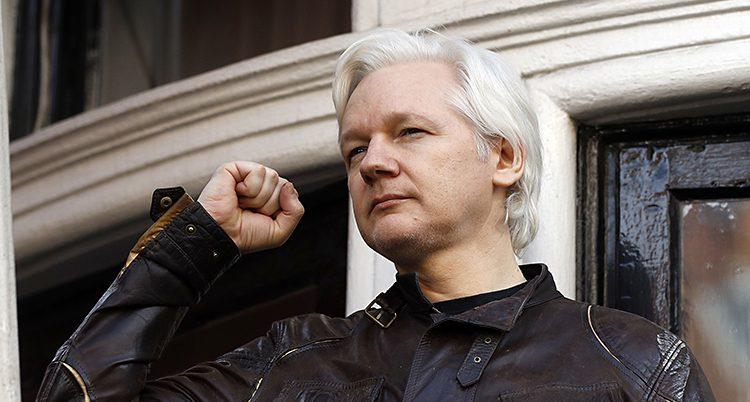 Julian Assange håller upp en näve i luften. Han har grått hår och en jacka av skinn på sig.