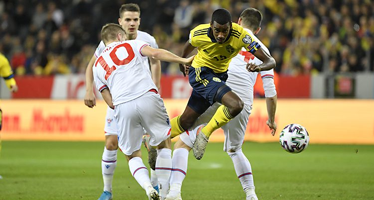 Från en fotbollsmatch mellan Sverige och Färöarna. Sveriges spelare Alexander Isak kämpar om bollen med en spelare från Färöarna. Isak har guld tröja och blå shorts. Den andra spelaren har vita kläder med röda siffror på ryggen.